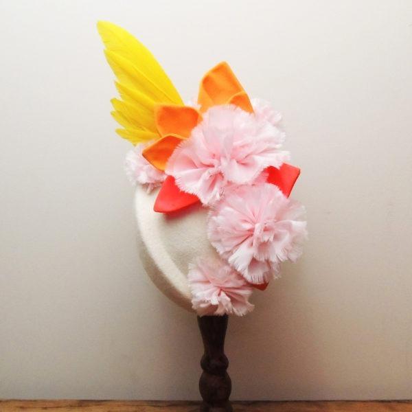 Petit chapeau de cérémonie rétro en feutre ivoire. Style vintage avec fleurs roses et feuilles oranges en tissu, et plumes jaunes Oh... Really? par Sandra Lacroix, chapelière, Bruxelles.
