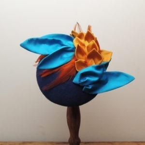 Chapeau de cérémonie rétro en feutre bleu royal. Style vintage avec plumes et décorations en tissu bleu, orange et jaune moutarde. Oh... Really? par Sandra Lacroix, chapelière, Bruxelles.