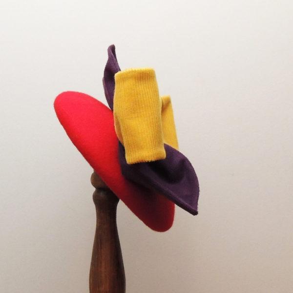 Bibi rond en feutre rouge rétro et de style vintage, avec nœud jaune et feuilles violettes en tissu. Oh... Really? par Sandra Lacroix, chapelière, Bruxelles.